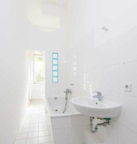 Badenzimmer mit Toiletten und einem Fenster, das auf einem Hof hinter dem Gebäude gibt