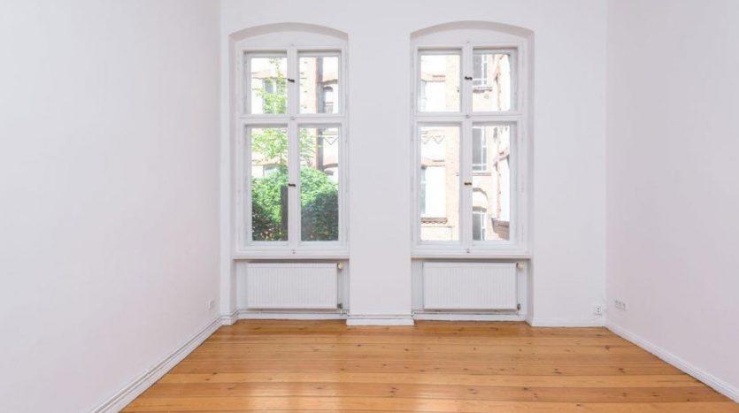 Zimmer mit zwei Fenstern, die auf einem Hof hinter dem Gebäude geben